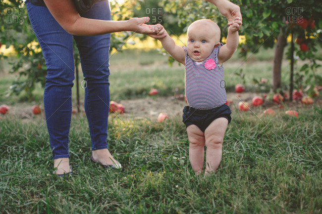 Mother helping infant daughter stand in an orchard