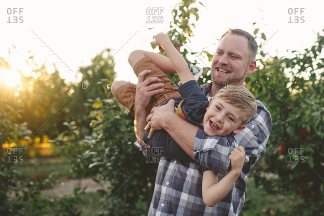 Father and son playing around in an orchard