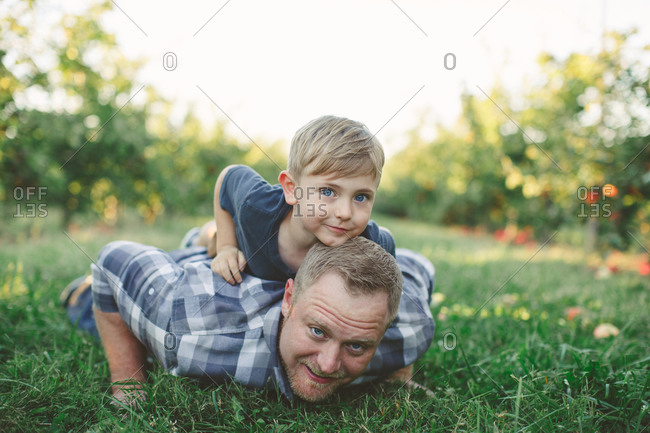 Father and son lying on the ground together in an orchard
