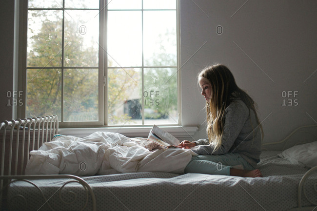A girl on her bed reading during the day
