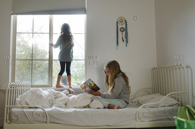 Girl reading on bed while sister looks out window