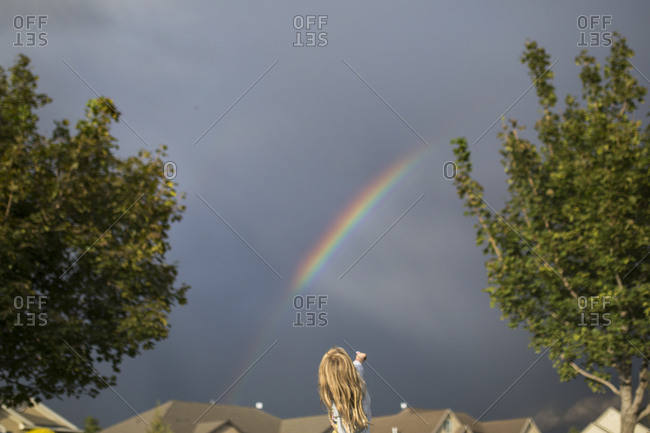 Girl pointing to a rainbow