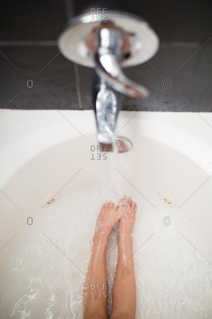 Feet of girl lying in a tub