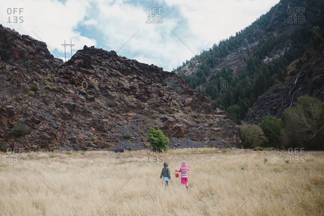 Two girls walking in a mountain field