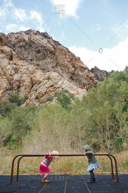 Girls on balance bars in mountain playground
