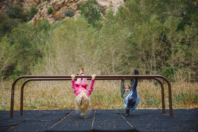 Girls hanging on bars in a mountain playground