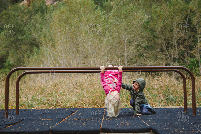 Girls hanging from bars in a mountain playground