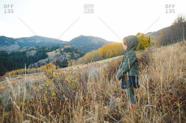 Girl in jacket staring across hill country