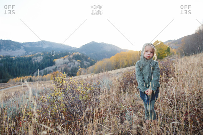 Girl standing on a rural hill wearing jacket