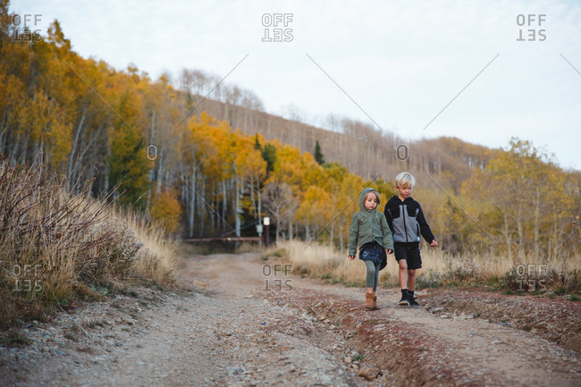 Boy and girl walking on dirt road in rural hills