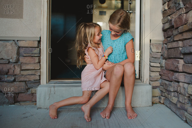Two sisters hugging and laughing sitting threshold