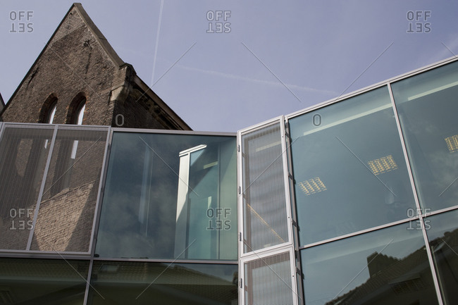 Ghent, Belgium June 6, 2007: Upward view of modern glass front office building incorporating element of historic chapel