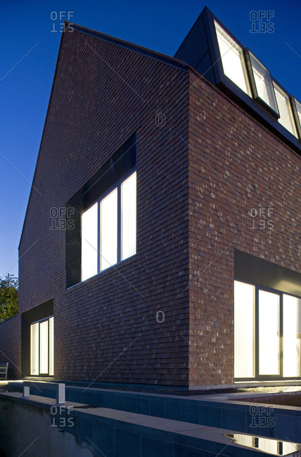 Sint-Martens-Latem, Belgium - September 4, 2008: Exterior of shingled office building at night with lighted windows