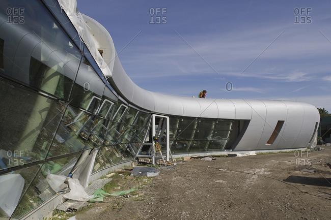 Kruibeke, Belgium - September 8, 2008: Man working on roof of modern curved building