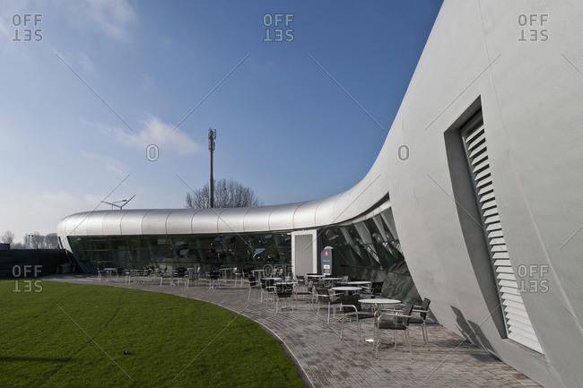 Kruibeke, Belgium - December 3, 2008: Tables and chairs set on patio of boomerang-shaped building