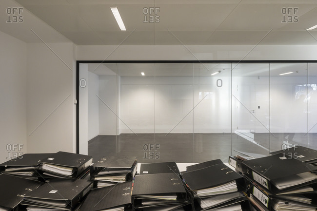 Ghent, Belgium - December 11, 2013: Binders stacked on a table inside an empty glass-walled office building