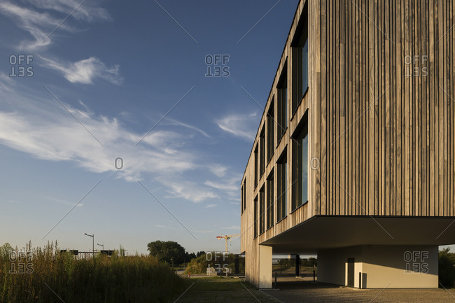 Ghent, Belgium - July 30, 2014: Vertical wood plank sided modern office building with parking beneath