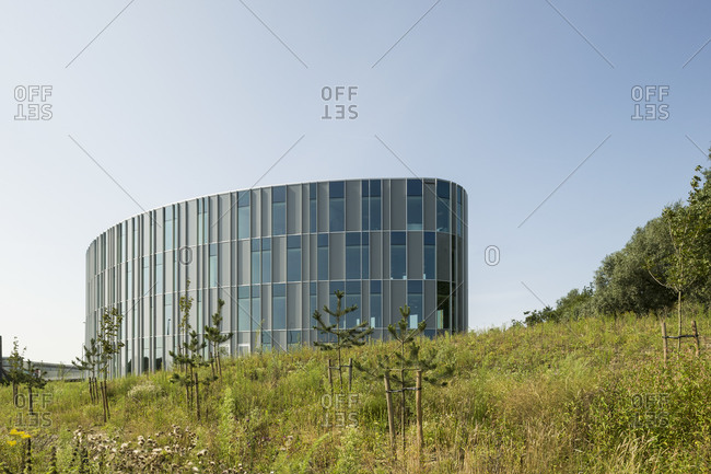 Ghent, Belgium - July 31, 2014: Organic-shaped building with rectilinear windows in field