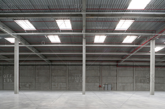 Empty warehouse with concrete walls and metal ceiling