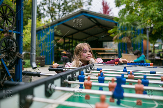 Girl with face paint playing foosball