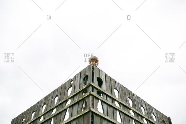 Little boy peeking from behind a fence