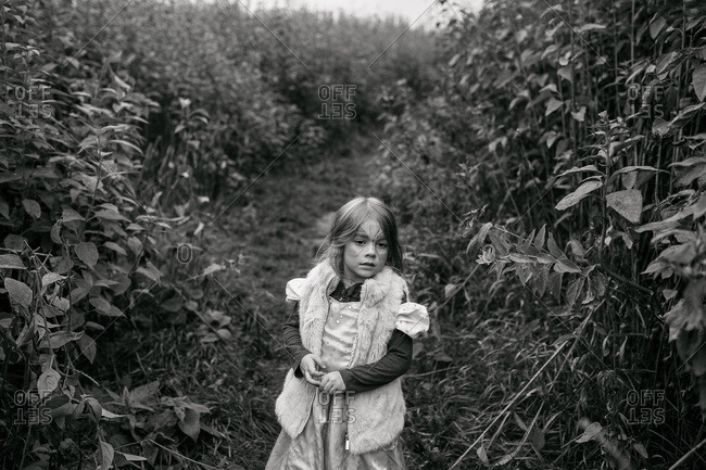 Girl with a painted face standing in a field