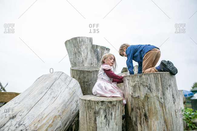 Boy and girl climbing on giant logs
