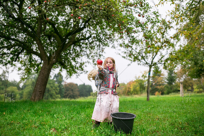 Girl with an apple at an orchard