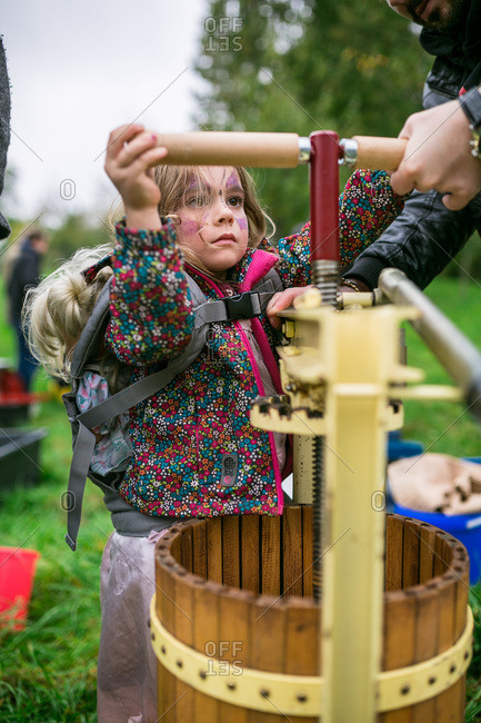 Girl using a cider press at an orchard