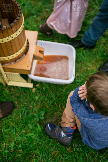 Kids watching a cider press in action