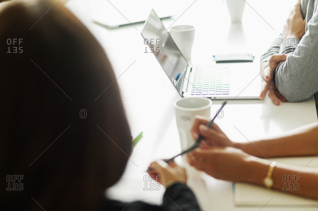 Hands of coworkers seated around a table