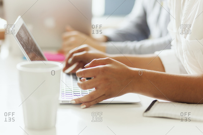 Hands of office employee with computer during meeting