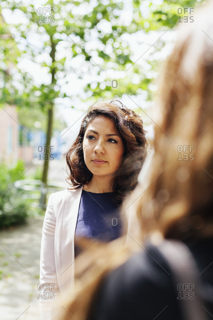 Businesswoman standing outside talking to colleagues