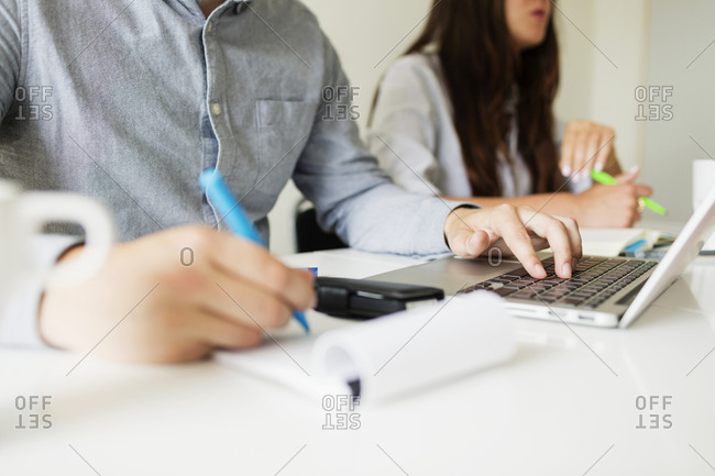 Midsection of male businessperson taking notes in meeting