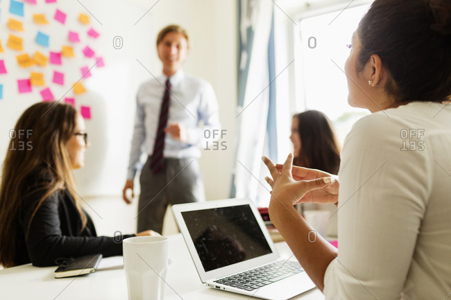 Female employee listening while colleague leads meeting