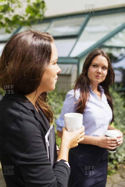 Businesswomen standing outside with coffee