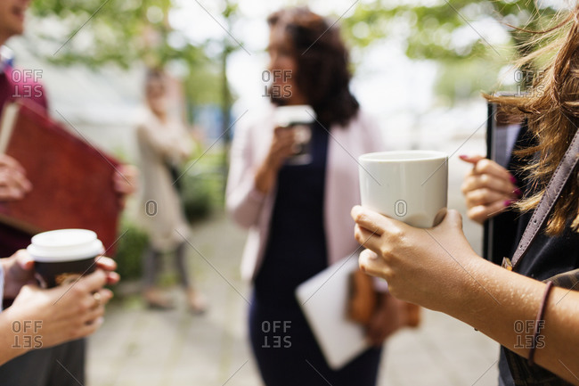 Businesspeople standing outside with coffee and laptops