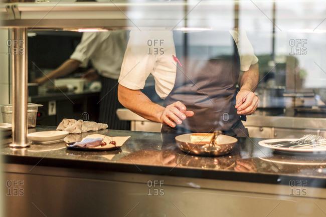 Chef preparing food behind a window in a restaurant kitchen