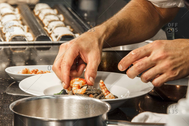 Chef's hands preparing a seafood dish