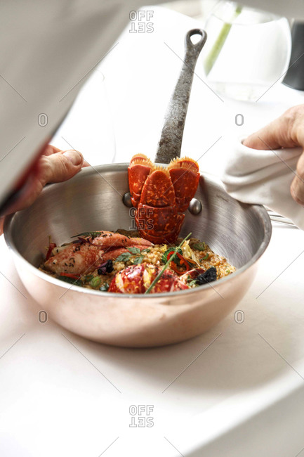 Hands wiping the lid of a pot with a seafood dish