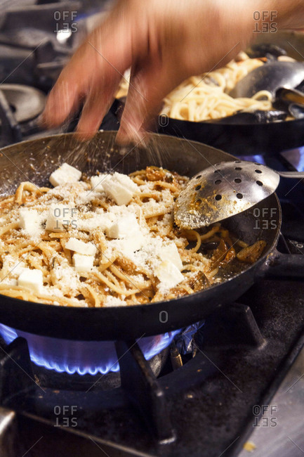 Chef adding cheese to a pasta dish on a stove