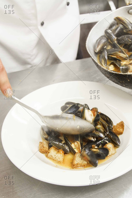 Chef spooning mussels onto a serving dish