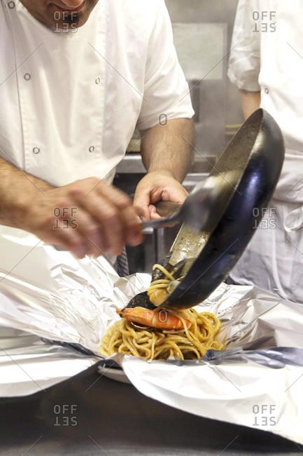 Chef spooning seafood pasta onto aluminum foil