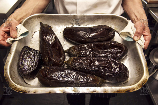 Chef holding roasted eggplants in a metal baking dish