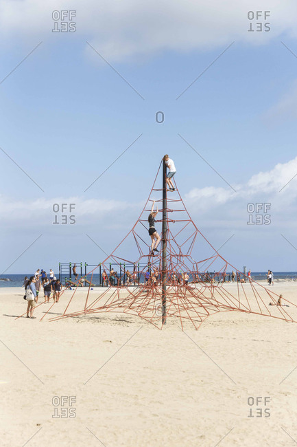 Adults scaling a climbing structure at a Barcelona beach