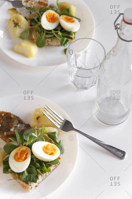 Soft-boiled eggs on toast with arugula