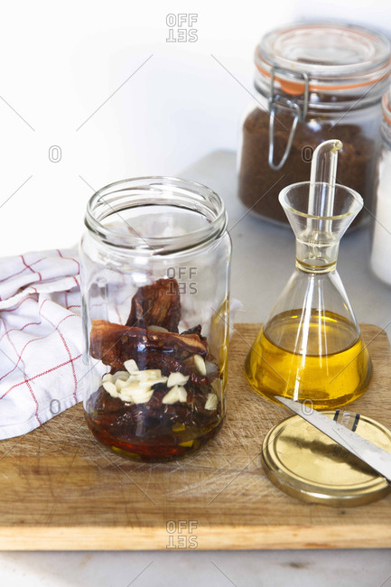 Peppers, garlic, and olive oil infusing in a jar