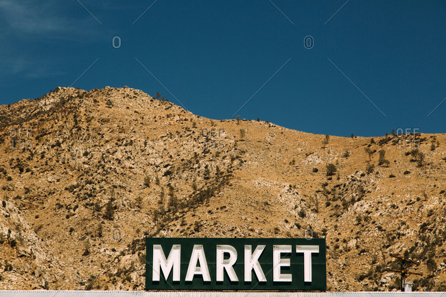 Sign for a market in front of arid mountainous terrain