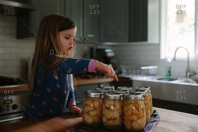 Little girl counting jars of canned apples