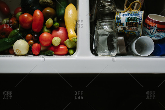 Sink full of fresh vegetables on one side and dishes on the other